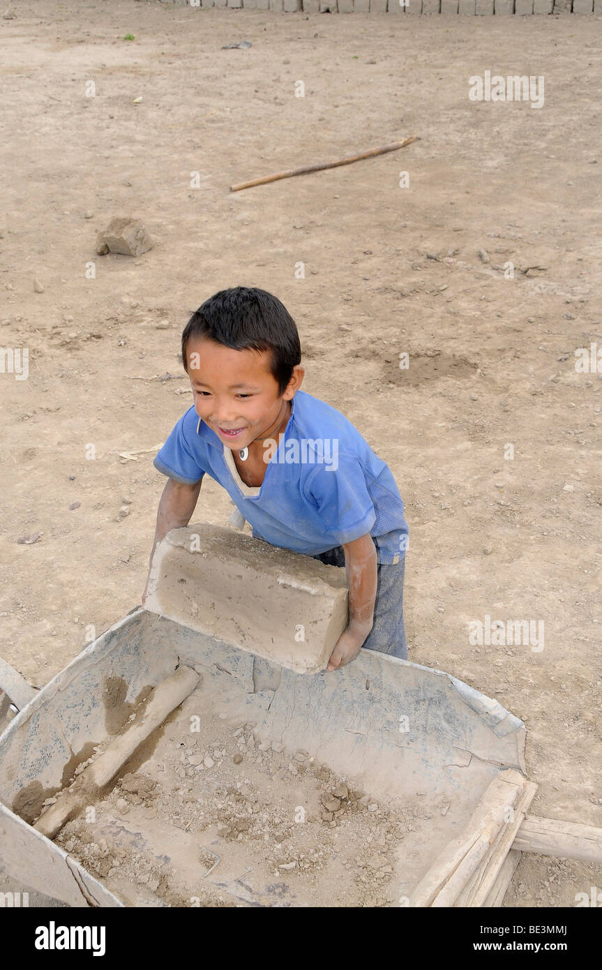Little boy loading a wheelbarrow with bricks in a brickyard that manufactures air-dried bricks in the Indus valley, - Stock Image