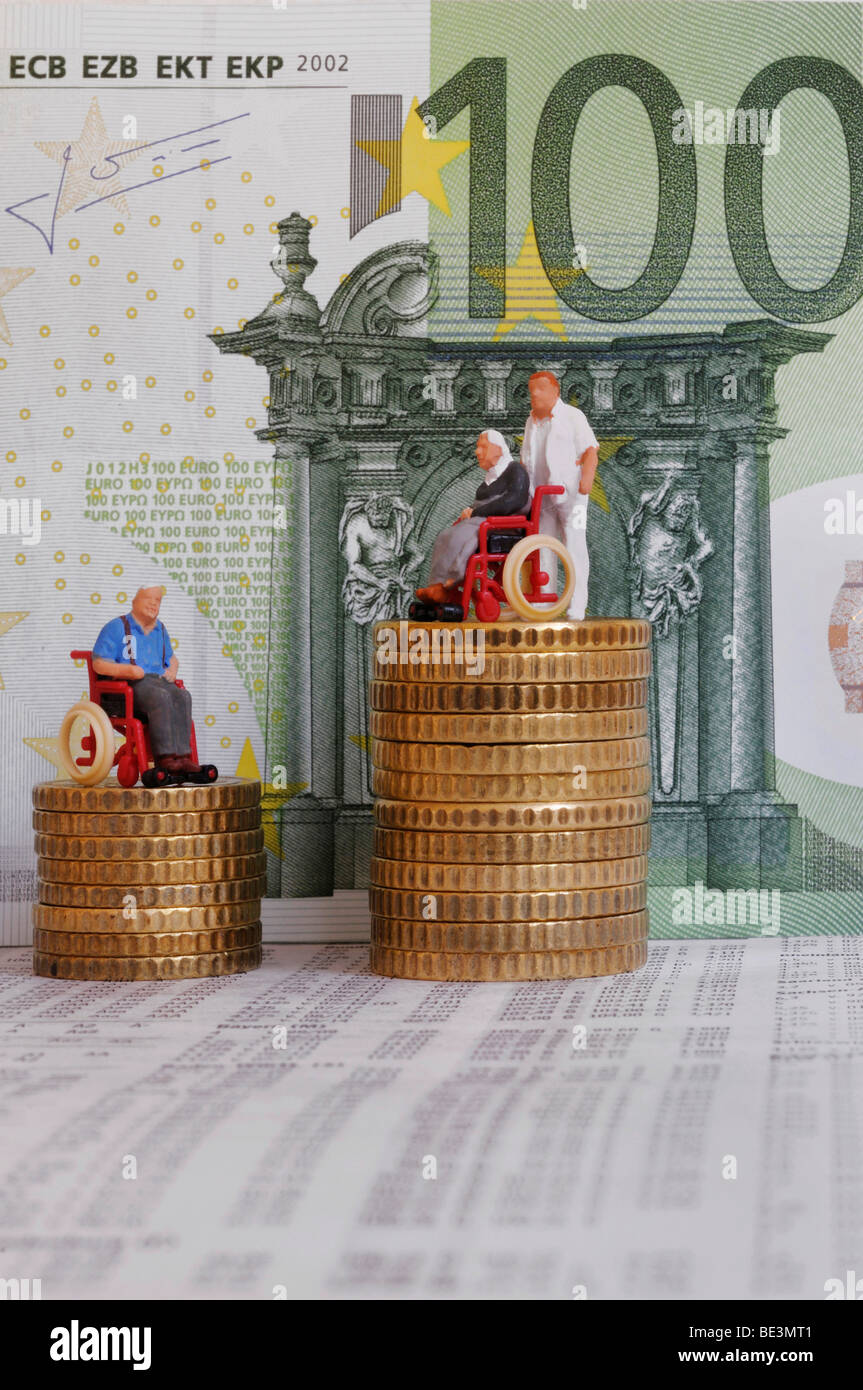 Figurine of a wheelchair-bound person on a stack of coins next to figurine of a carer pushing a wheelchair, in the - Stock Image