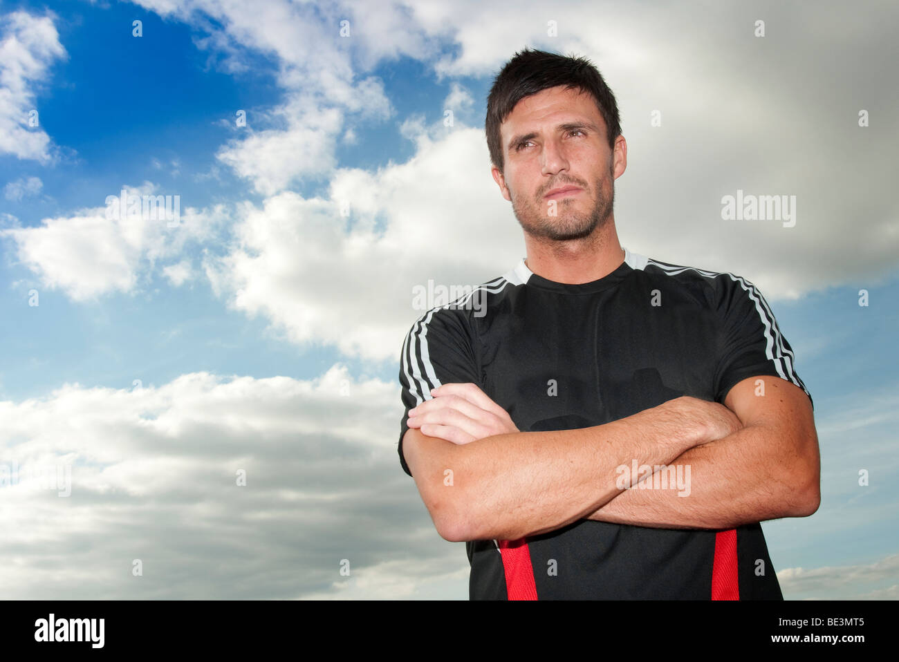 footballer standing with arms folded - Stock Image