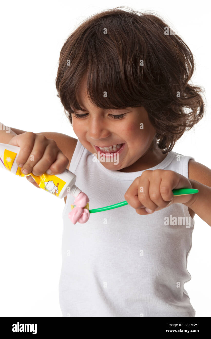 Little boy is putting a lot of toothpaste on his toothbrush - Stock Image