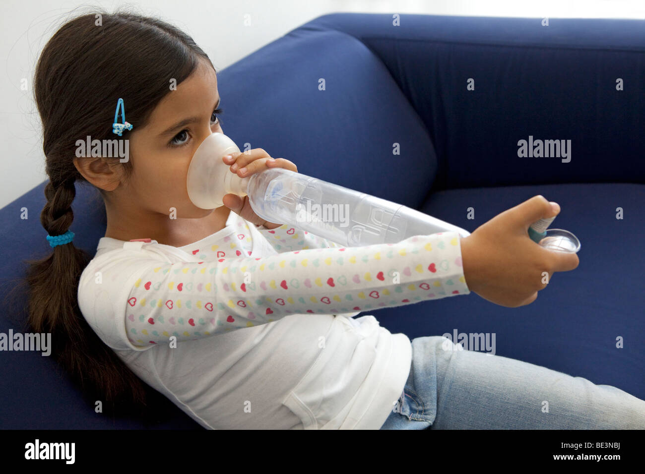 Little girl with an inhaler - Stock Image