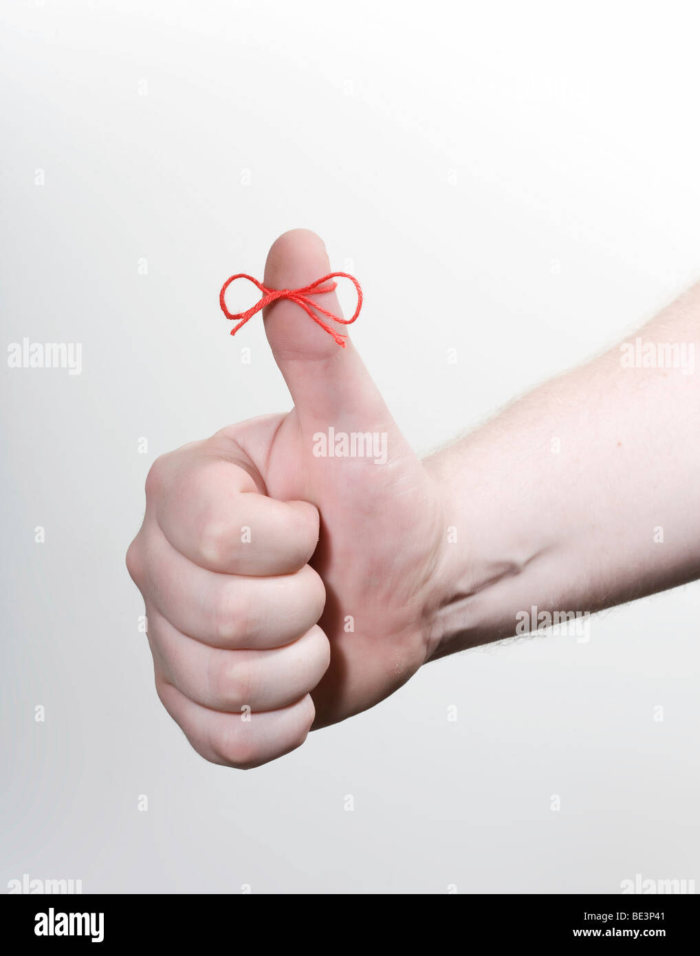 Thumbs up with a red string bow, memory Stock Photo