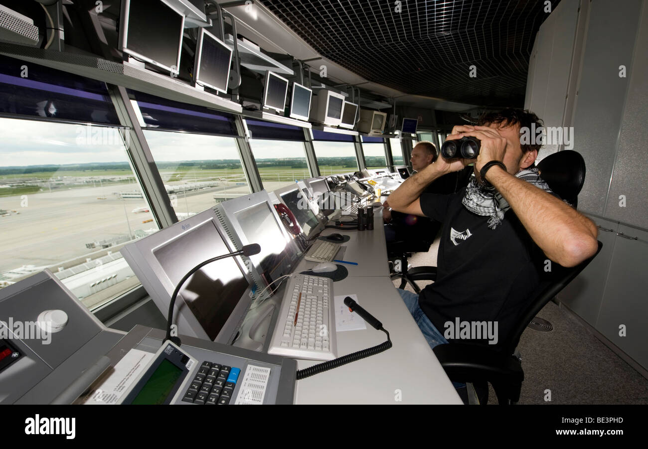 Two air-traffic controllers in 78 m high main tower of Munich Airport looking on to the apron West and Terminal - Stock Image