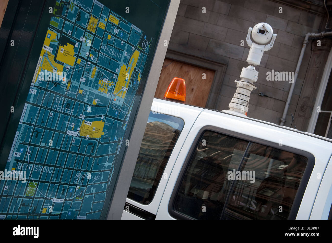 A mobile CCTV van parked next to a map of Glasgow City Center outside Glasgow Central Station. - Stock Image