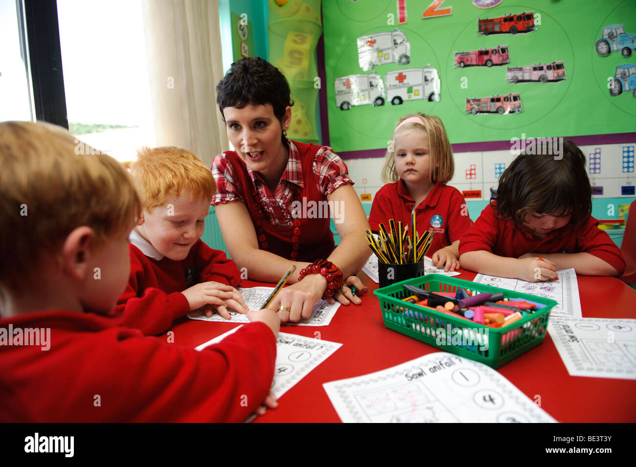 young woman teacher in a welsh language primary school teaching mathematics to young children wales
