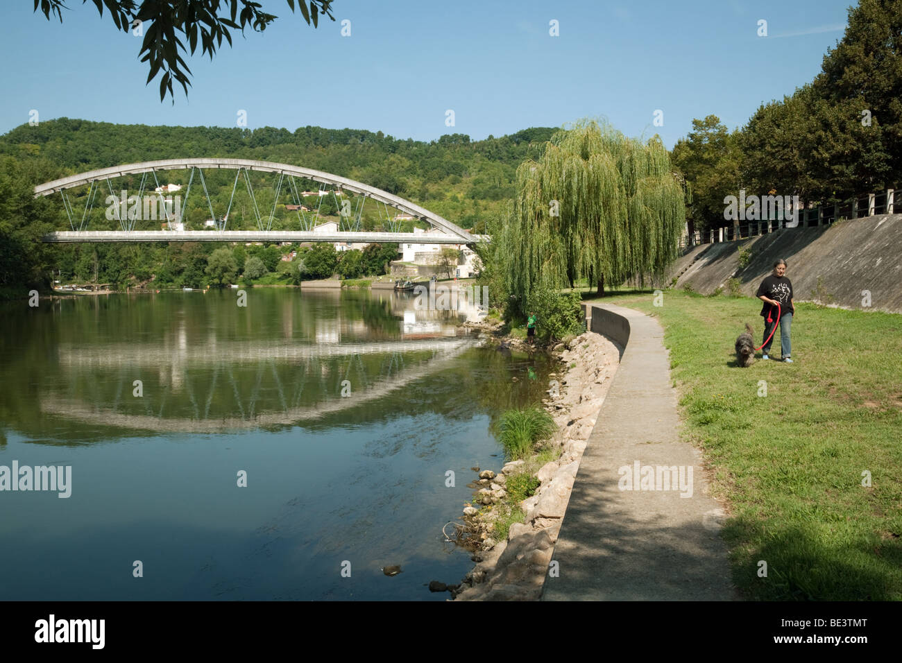 A woman walking her dog with, in the background, the bridge across the river Lot at Castelmoron sur Lot, Aquitaine, - Stock Image