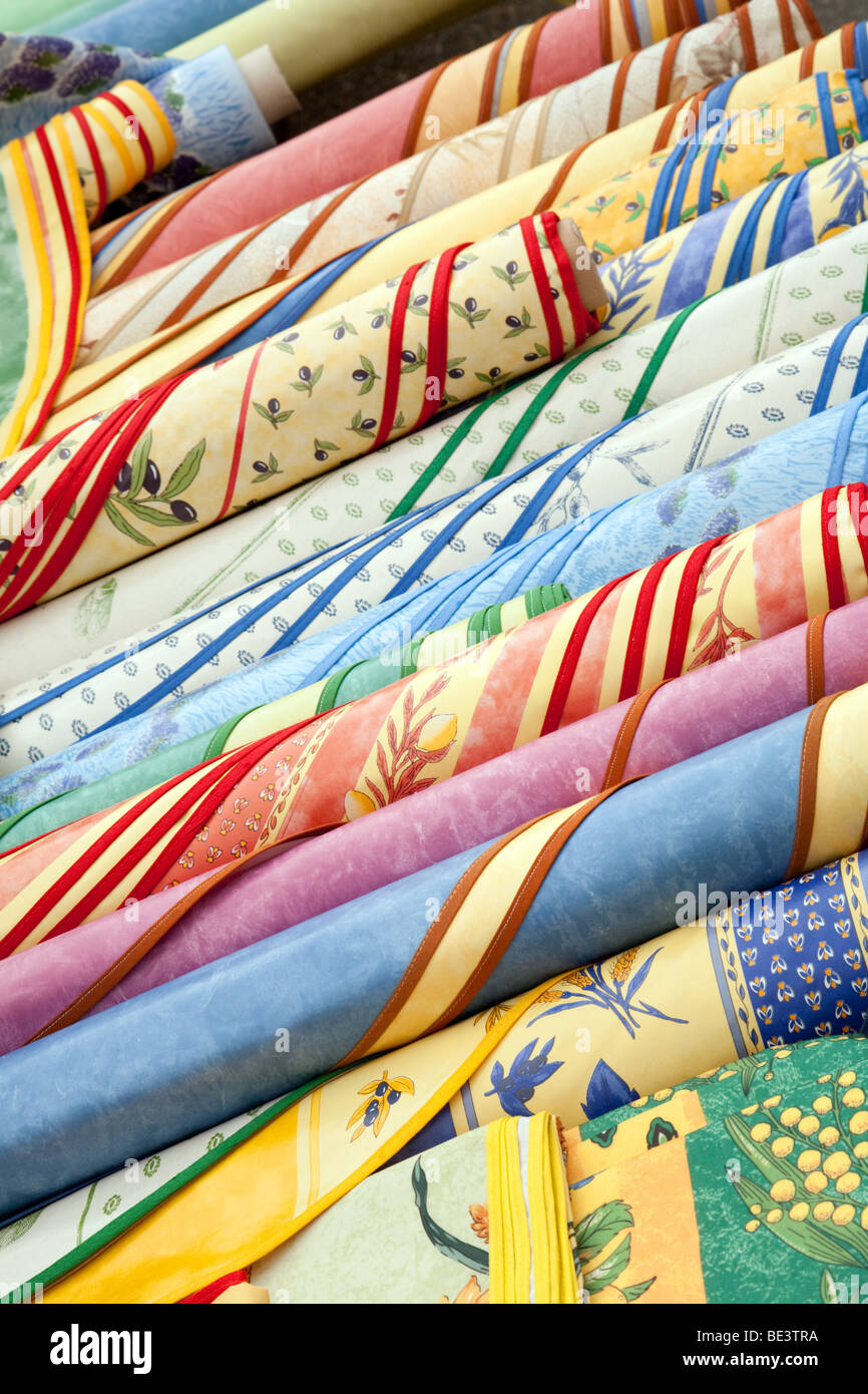 Colourful rolls of material for sale in the market in the French town of Nerac, Aquitaine, France - Stock Image