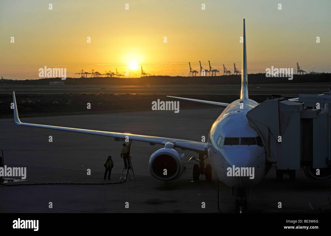 Qantas Airlines Boeing 717 refueling at sunrise, Brisbane International Airport, cranes in the rear, harbour, Brisbane, - Stock Image