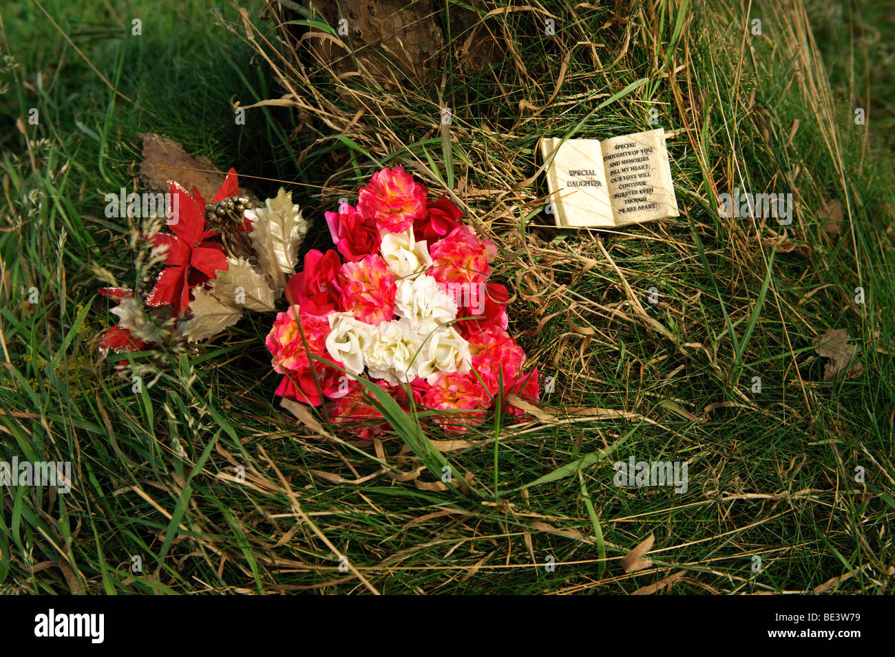 Arrangement of flowers on the ground left as a floral tribute to a dead daughter, UK - Stock Image