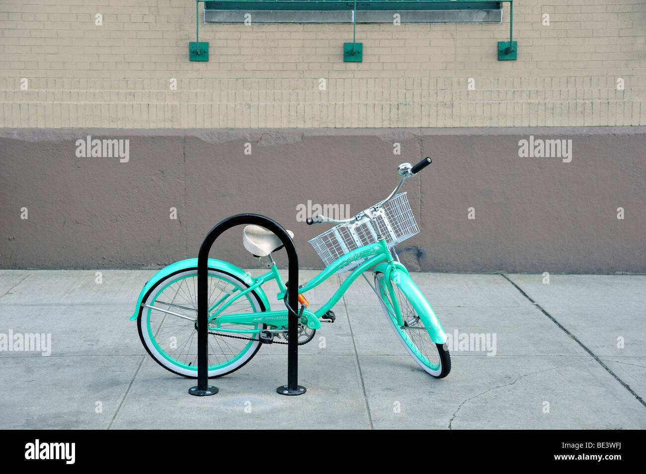 A women's turquoise green open frame Beach Cruiser style bicycle with a basket on the handlebars, locked to a bicycle Stock Photo