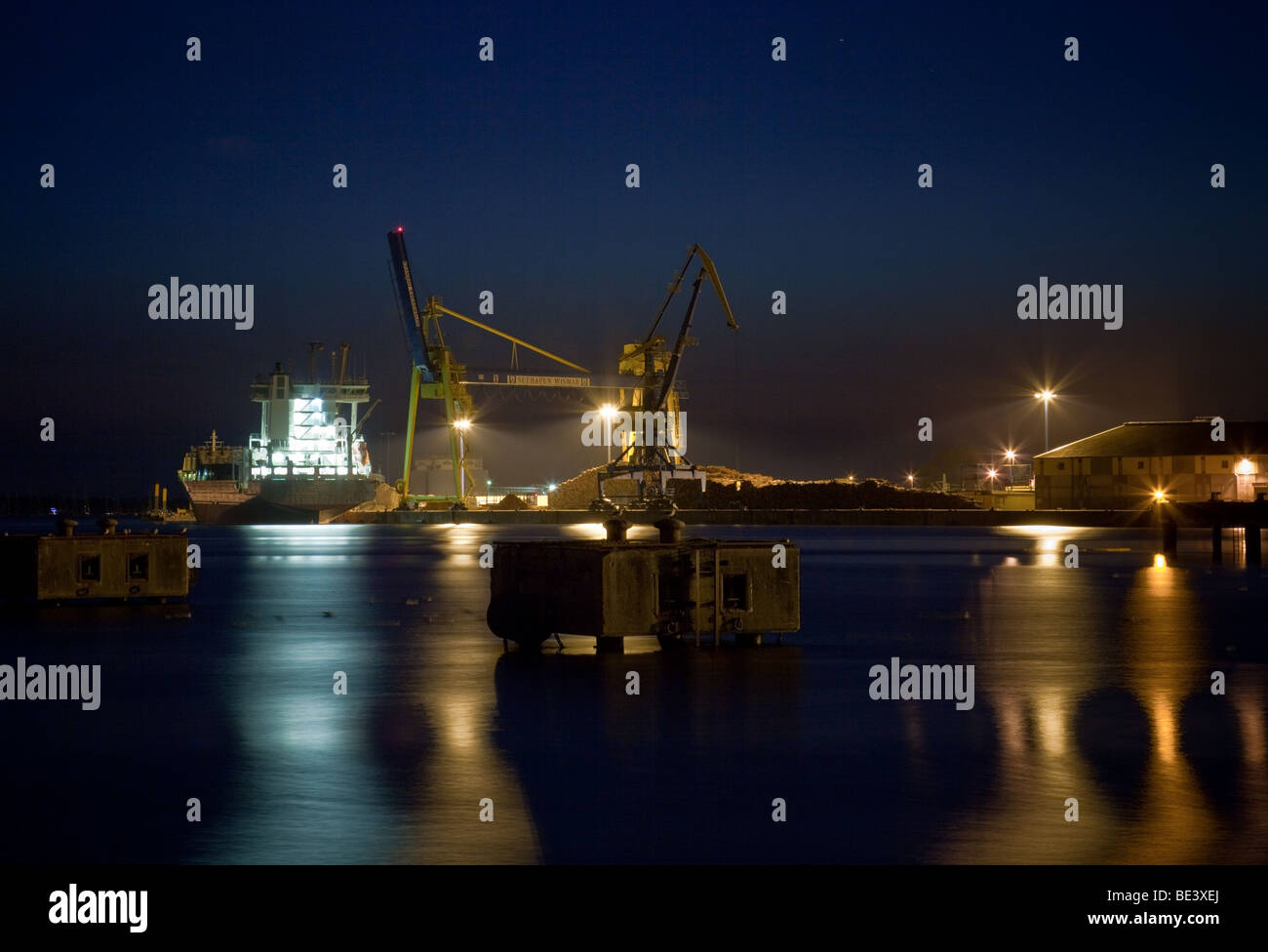 Harbor of Wismar, Germany, with ship and cranes by night - Stock Image