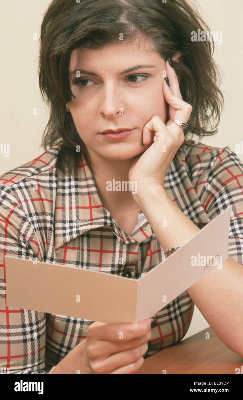 Sad woman holding postcard in hand and looking up from the greeting card that made her sad SerieCVS100024101 - Stock Image