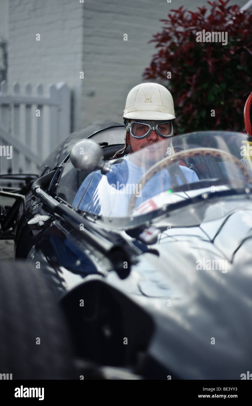 Driver in period dress waits in his historic racing car - Stock Image