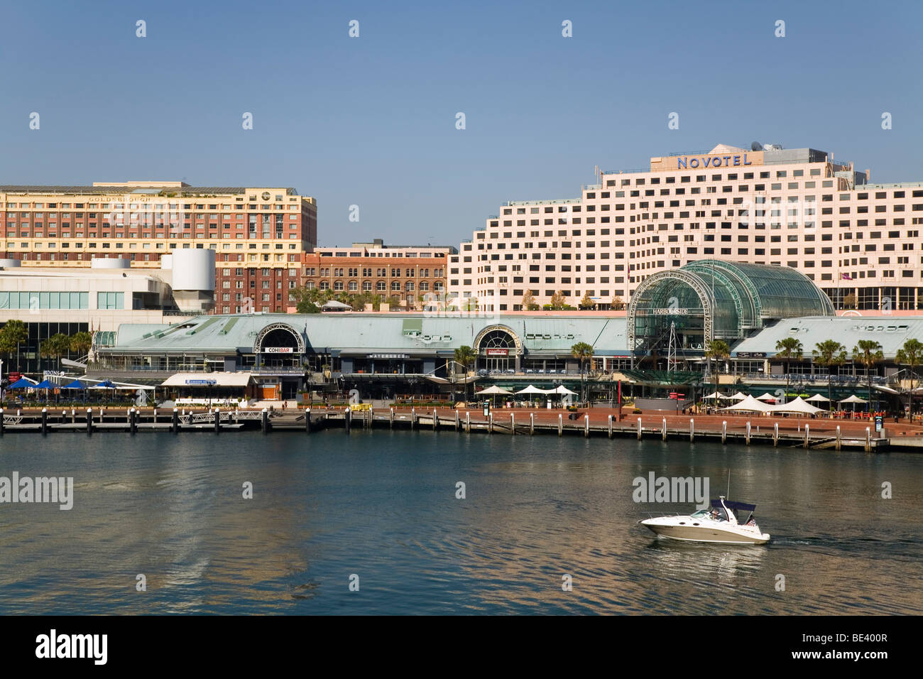 A boat motors into Cockle Bay with the Harbourside Complex in the background. Darling Harbour, Sydney, New South - Stock Image