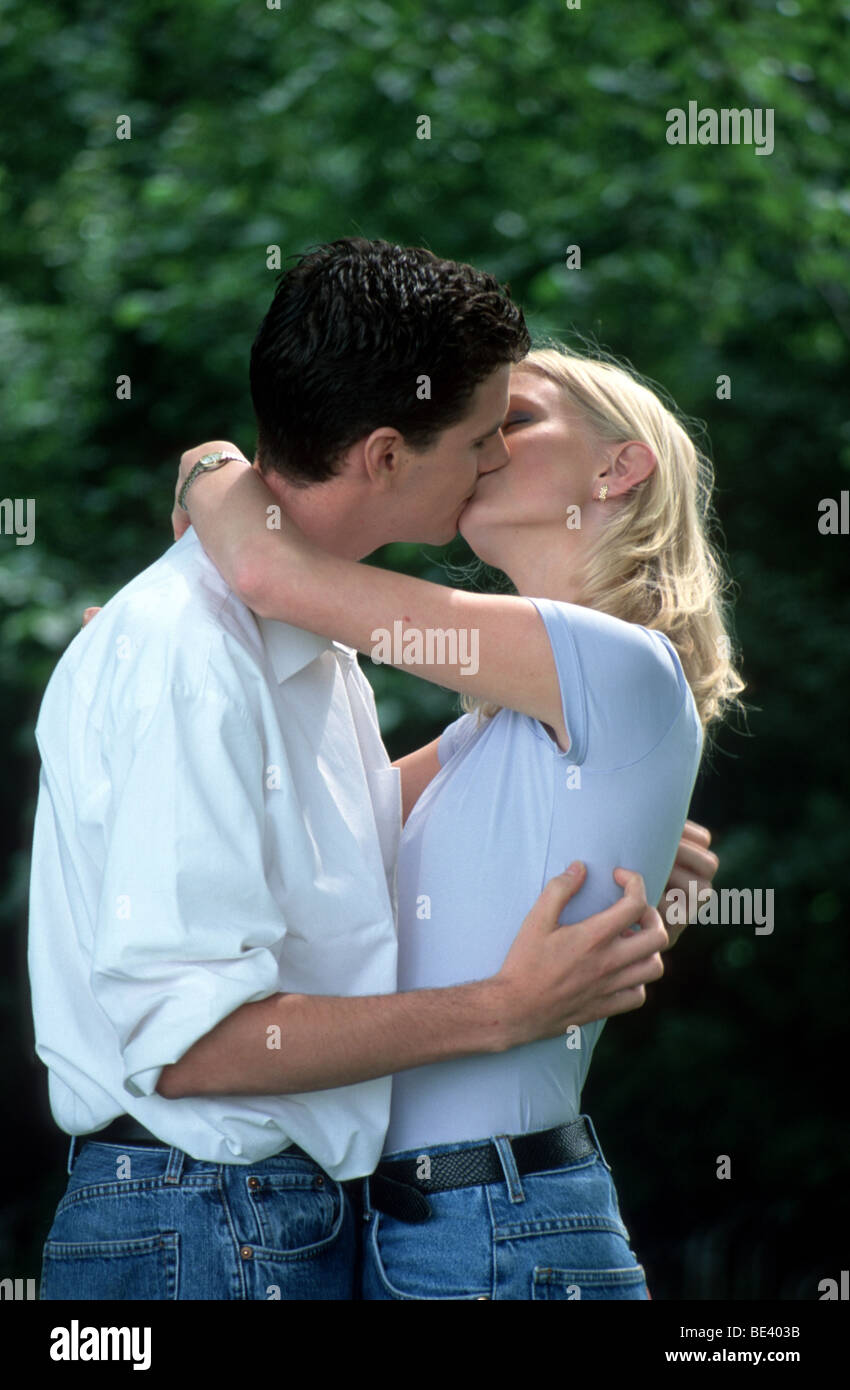 Couple young man and woman embracing and kissing  - Couple in love in park - Stock Image