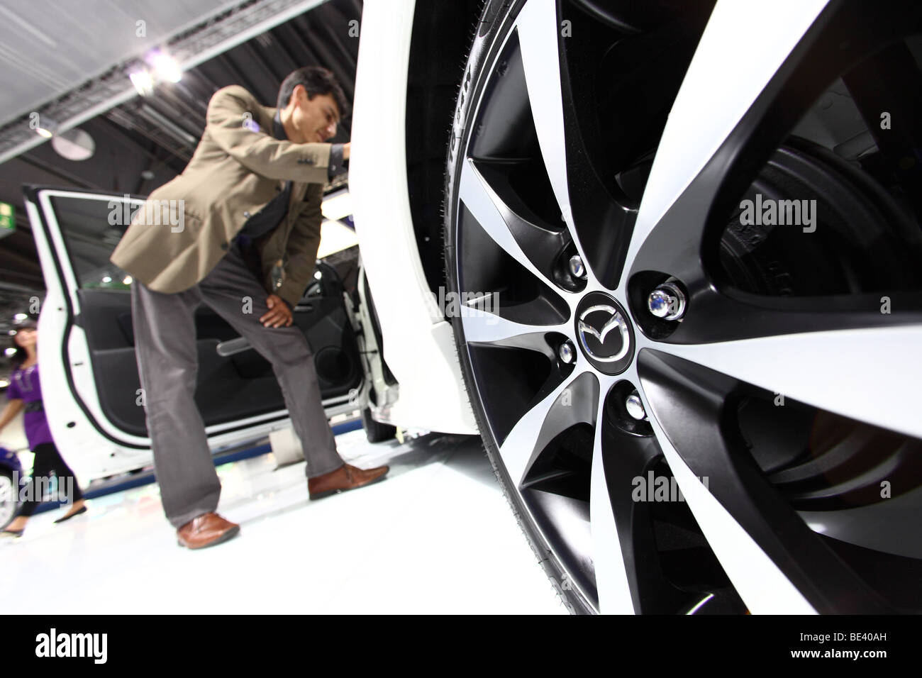 63th International Motor Show ( IAA ): A visitor is interested in a car of the manufacturer Mazda - Stock Image