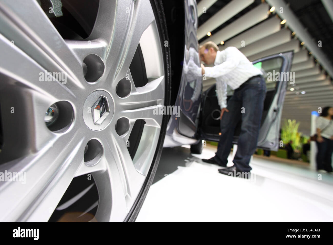 63th International Motor Show ( IAA ): A visitor is interested in a car of the manufacturer Renault - Stock Image