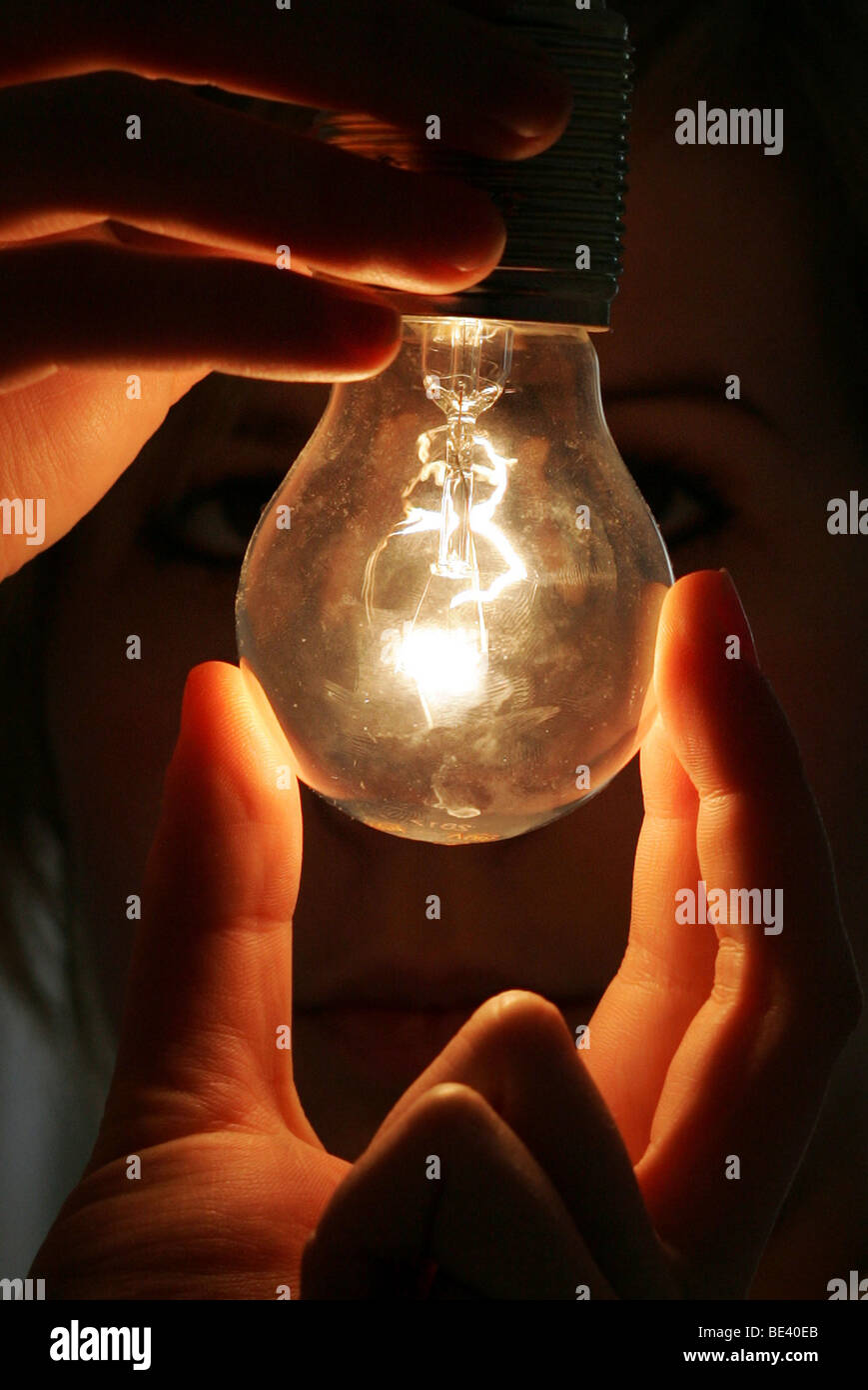 YOUNG WOMAN SCREWING  A  LIGHT BULB. Stock Photo