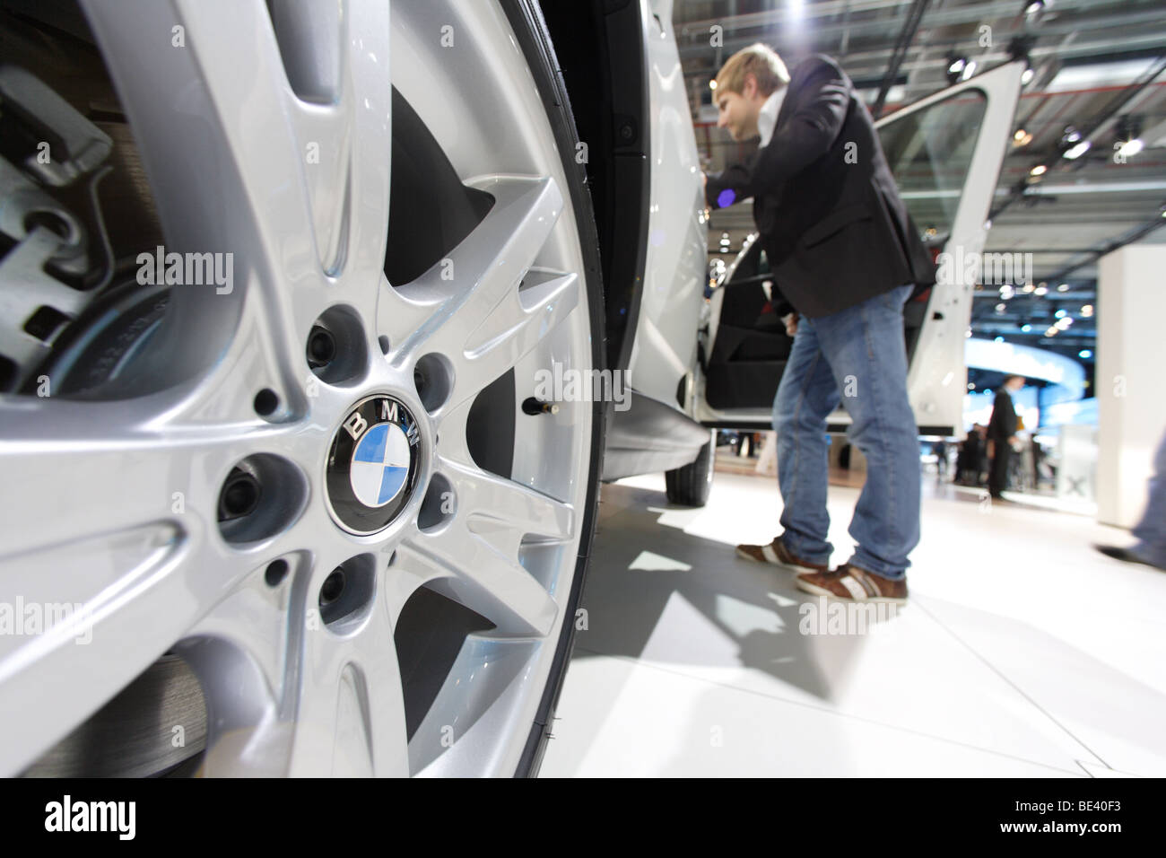 63th International Motor Show ( IAA ): A visitor is interested in a car of the manufacturer BMW - Stock Image