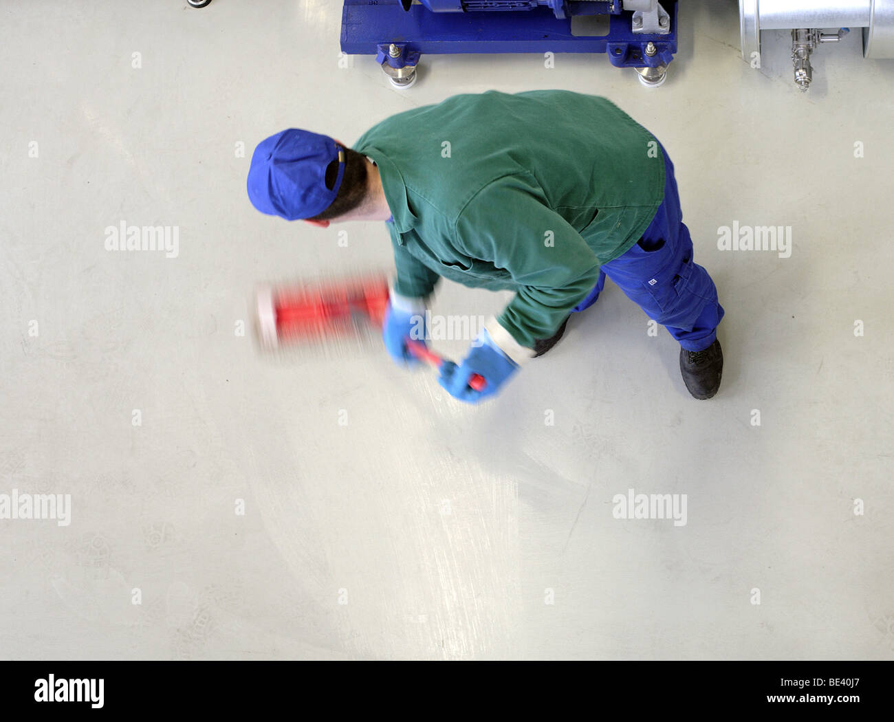 MAN AT WORK. CLEANING THE FLOOR. Stock Photo