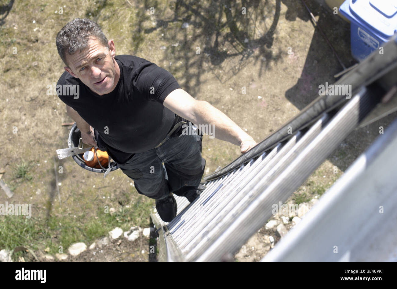 A SLATER CLIMBING ON A  ROOF. - Stock Image