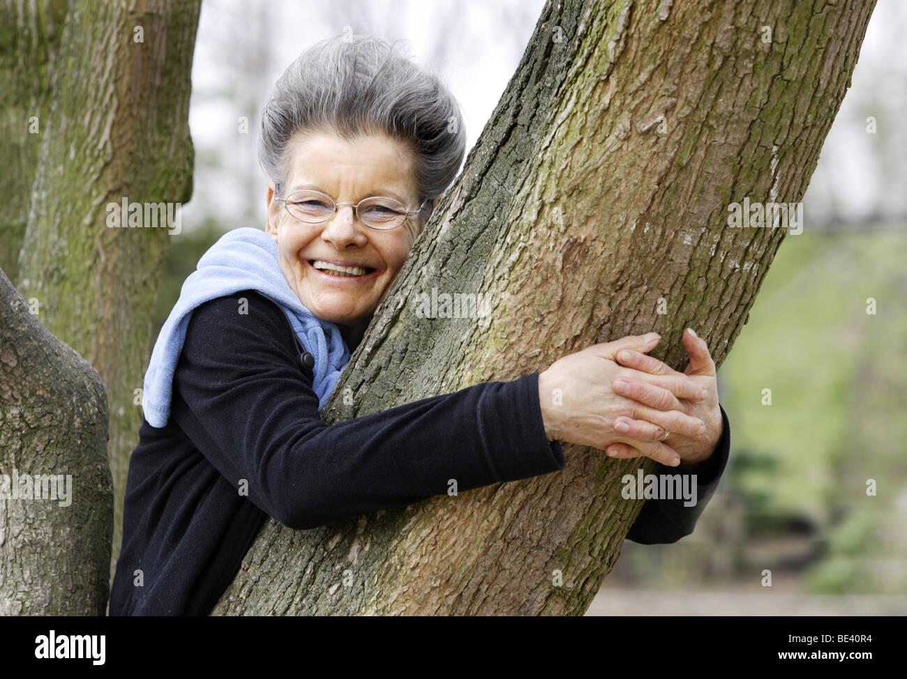 Seniorin lehnt an einen Baum Stock Photo
