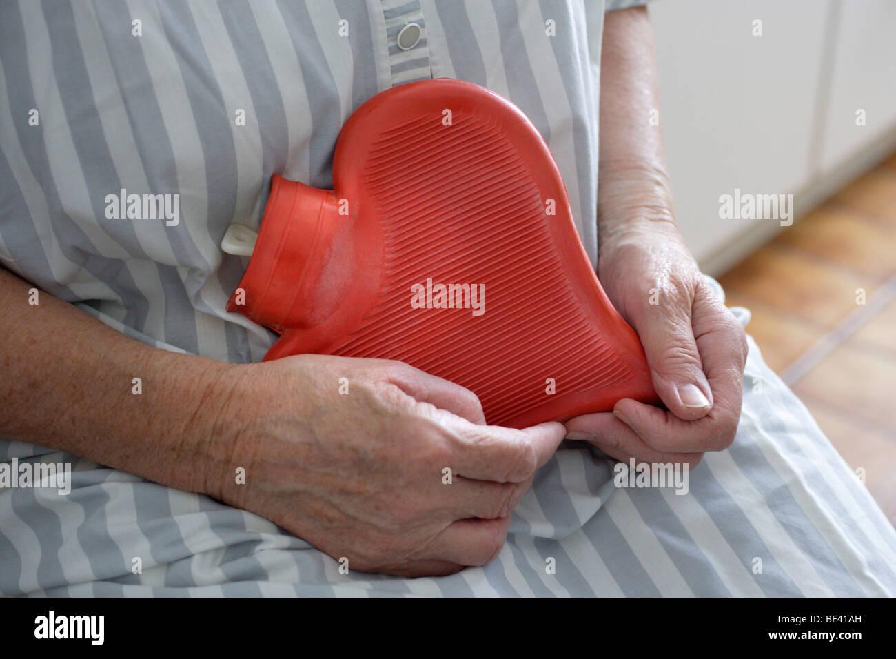 Pflegefall , Gesundheitssystem . Seniorin mit einer Herzwaermflasche . Stock Photo