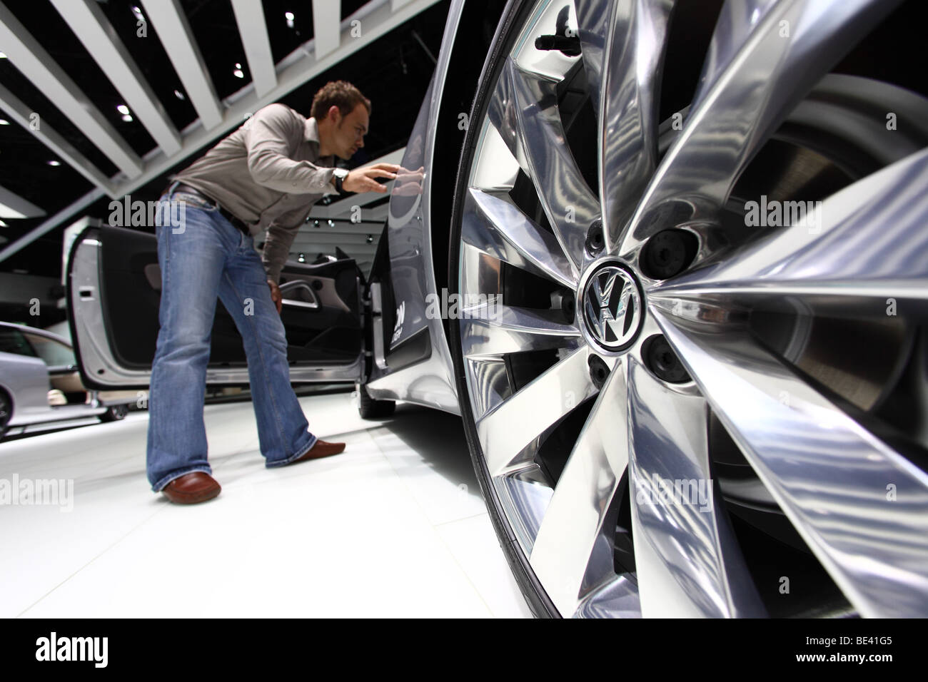 63th International Motor Show ( IAA ): A visitor is interested in a car of the manufacturer Volkswagen - Stock Image