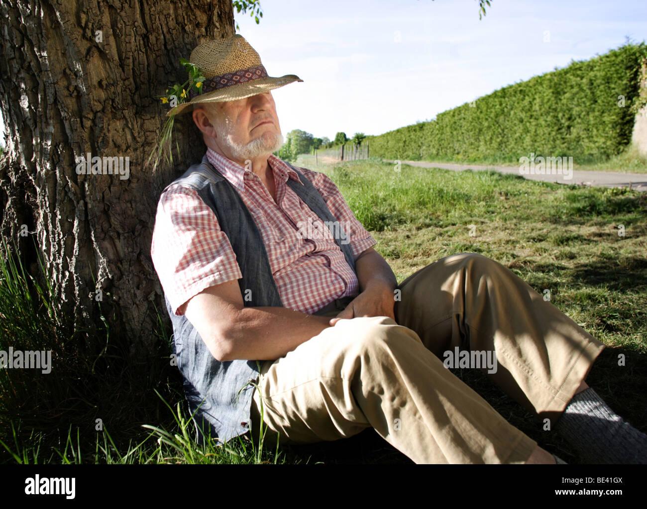 Ein Rentner sitzt unter einem Baum . Heidelberg Stock Photo