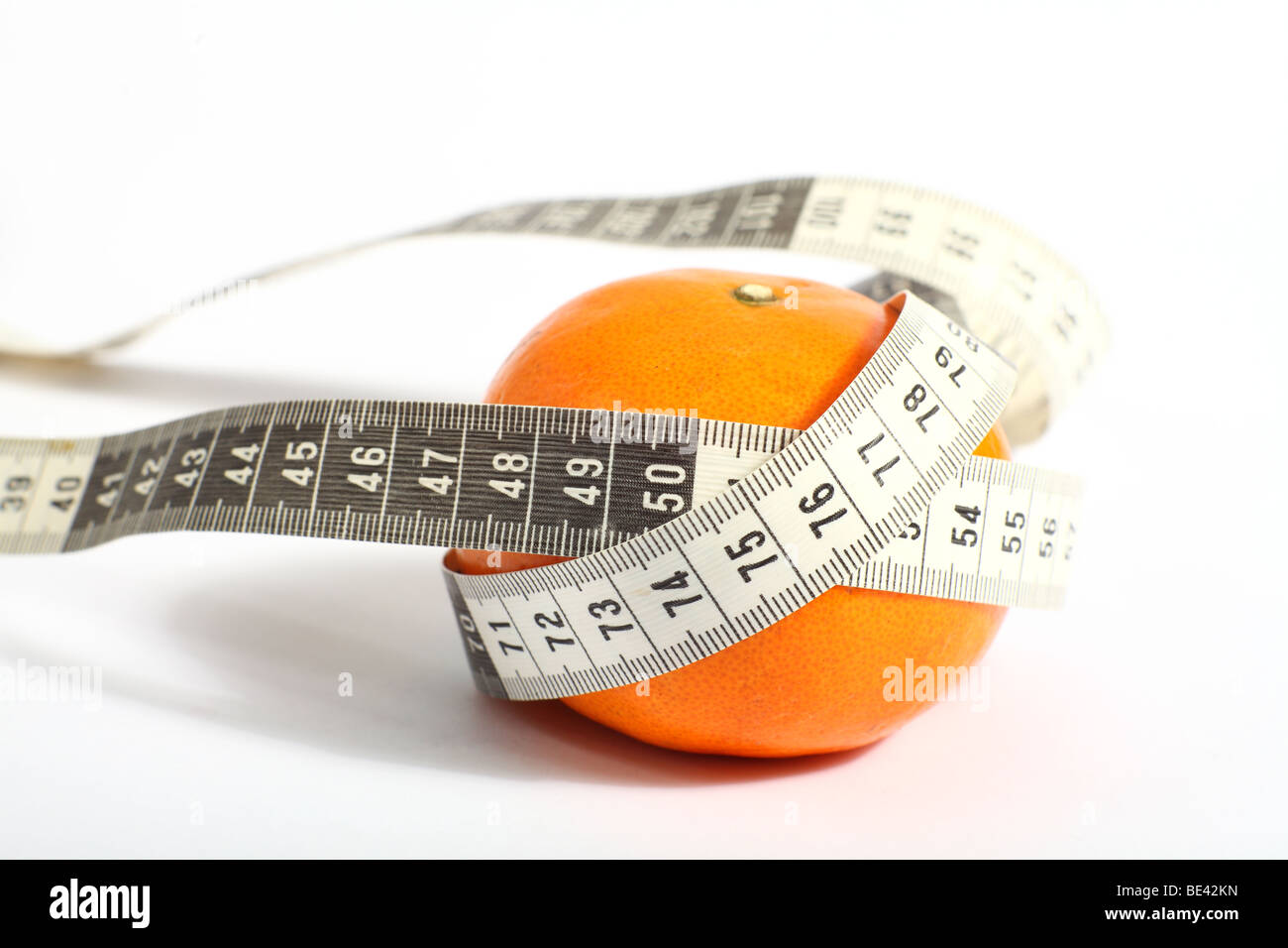 A dressmaker's tape measure, showing metric measurements, with a tangerine, symbolising a healthy diet of fruit - Stock Image
