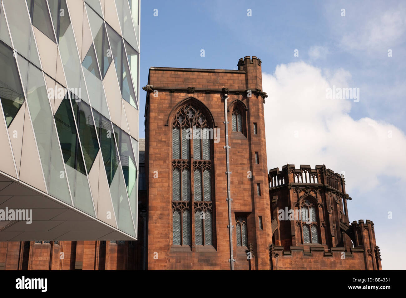 Modern glass building by John Ryland's Library in old building near the city centre. Deansgate, Manchester, - Stock Image