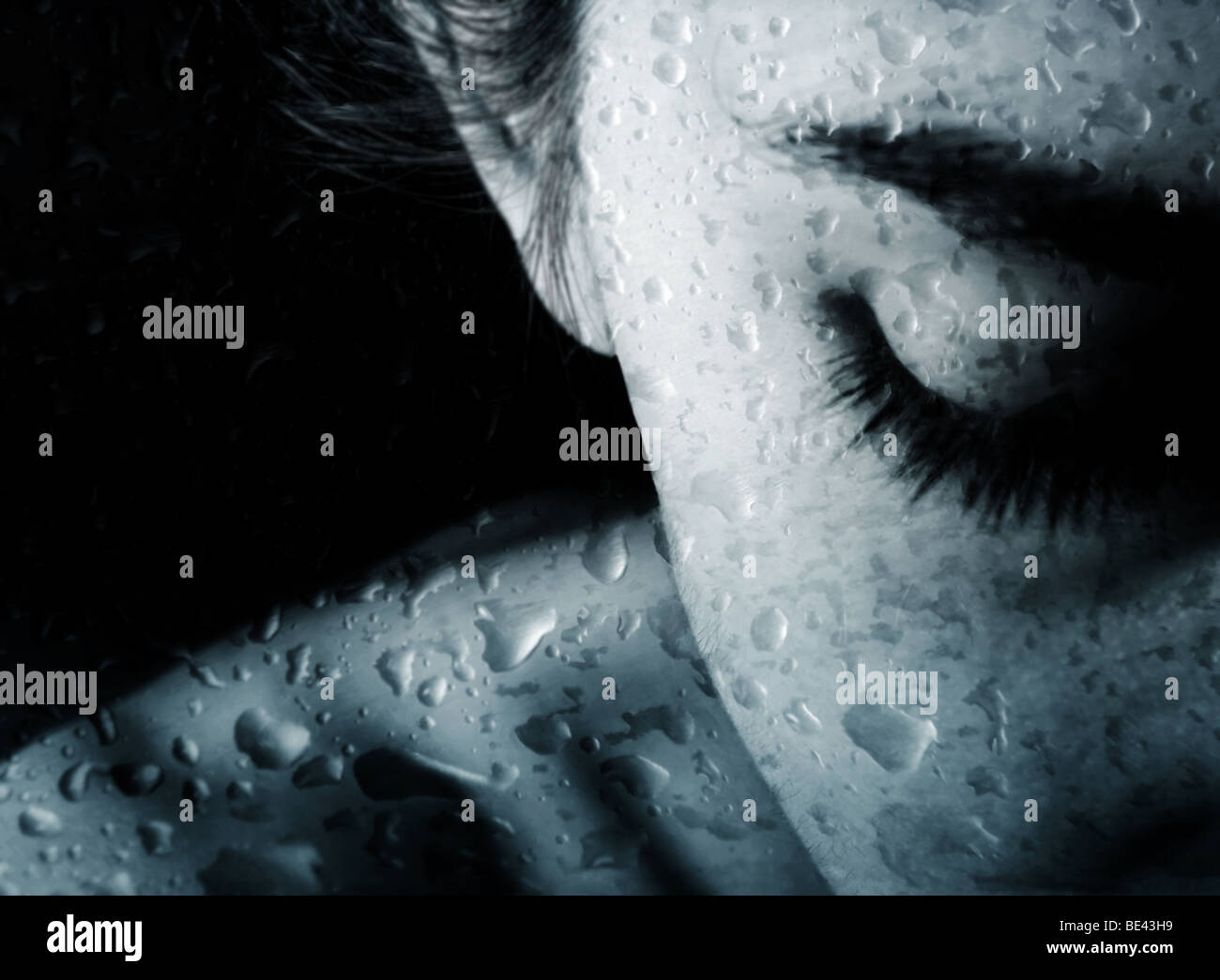 Young woman behind the glass with the drops of rain - Stock Image