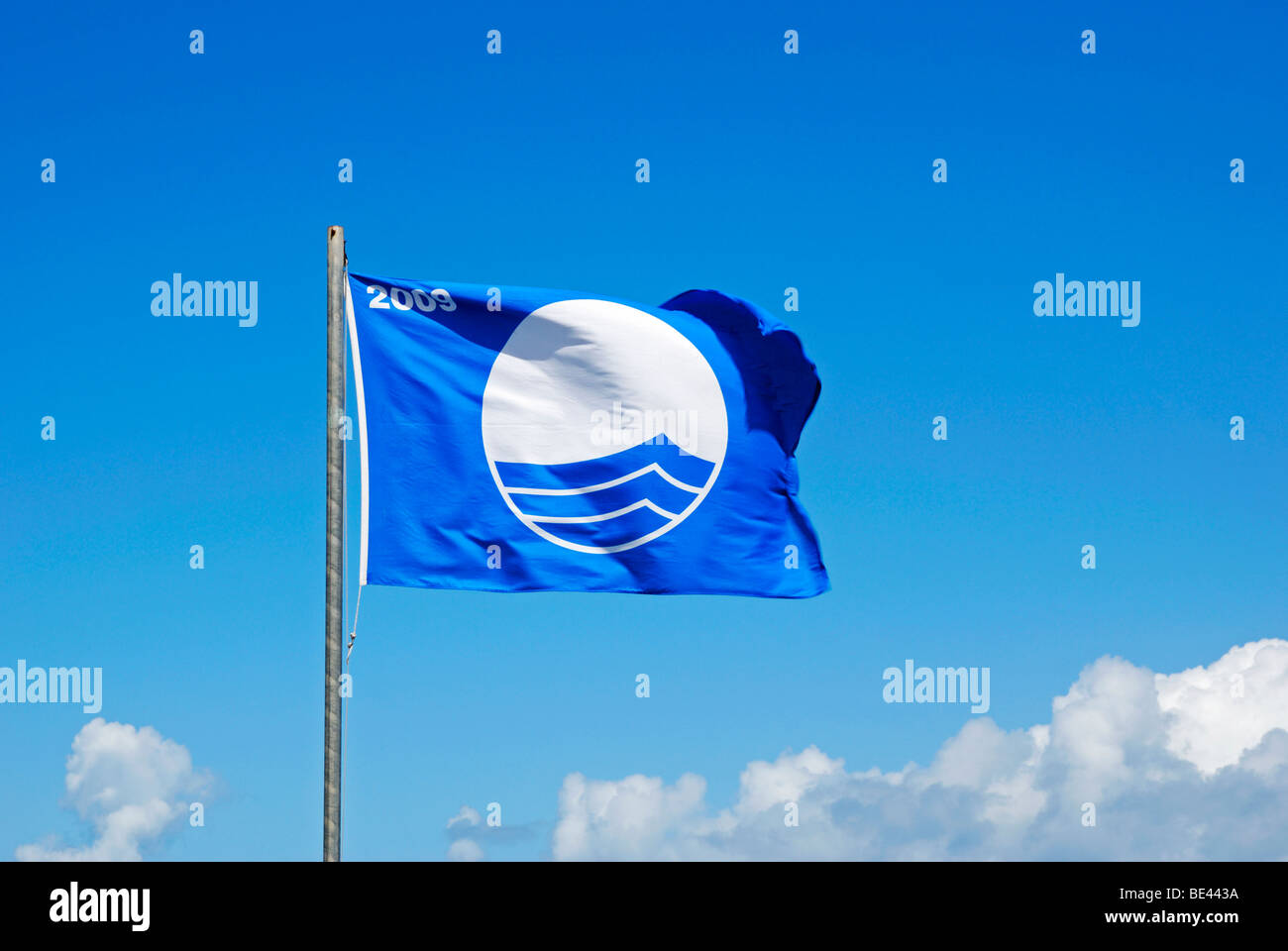 the blue flag awarded for beach and water cleanliness flying over porthmeor beach in cornwall, uk - Stock Image