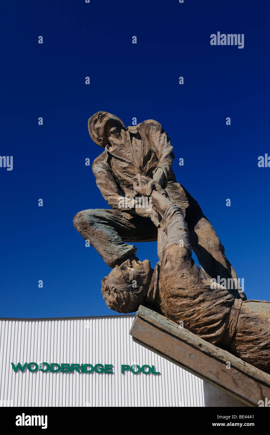 Sculpture of hero pulling a worker to safety at a construction accident at Woodbridge Pool Vaughan Ontario Canada - Stock Image