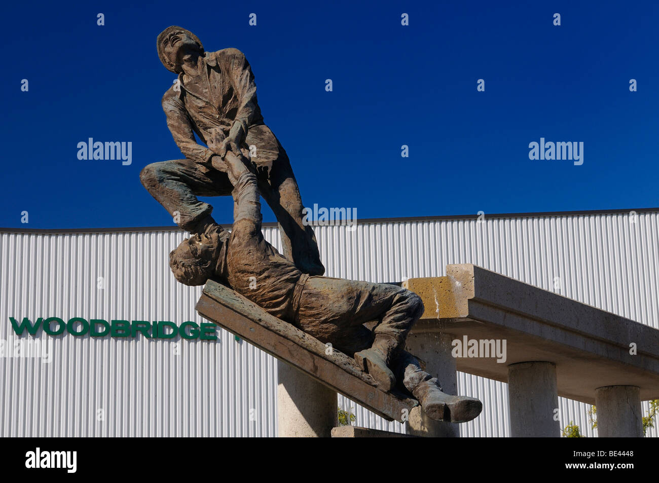 Sculpture of hero saving a construction worker with blue sky at Woodbridge Pool and Memorial Arena Vaughan Ontario - Stock Image