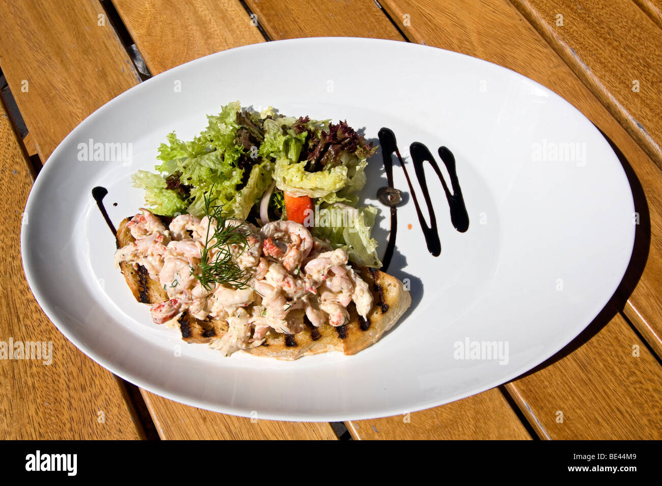 Typical open faced Norwegian sandwich featuring shrimp salad and greens. - Stock Image