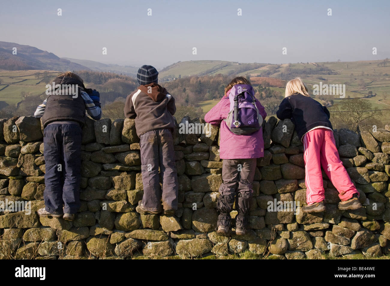 Four children taking a break from their walk, perching and leaning on a dry stone wall, admiring the view over Wharfedale. - Stock Image