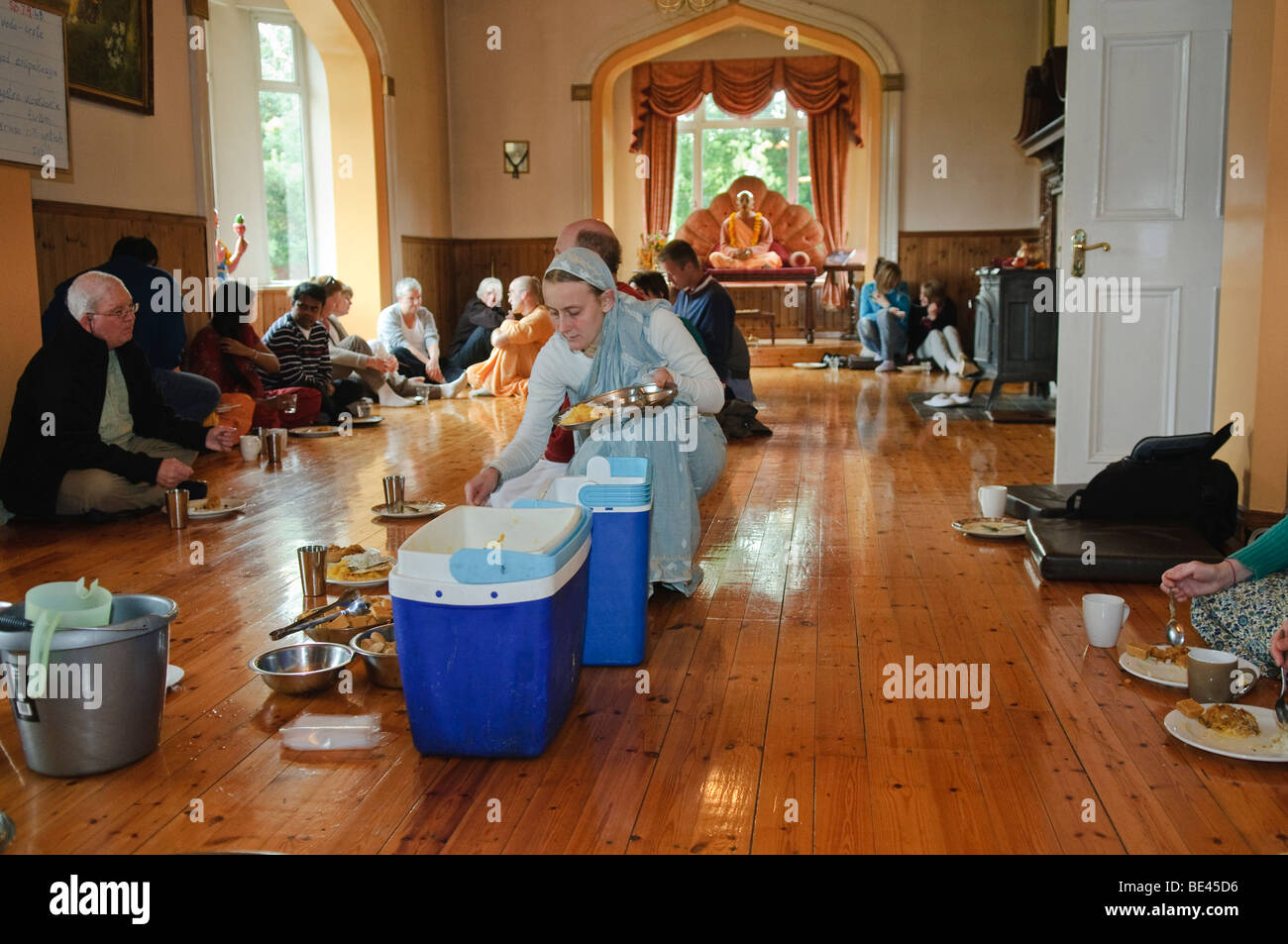 Disciples and visitors eating a vegetarian feast at a Hare Krishna temple room Stock Photo