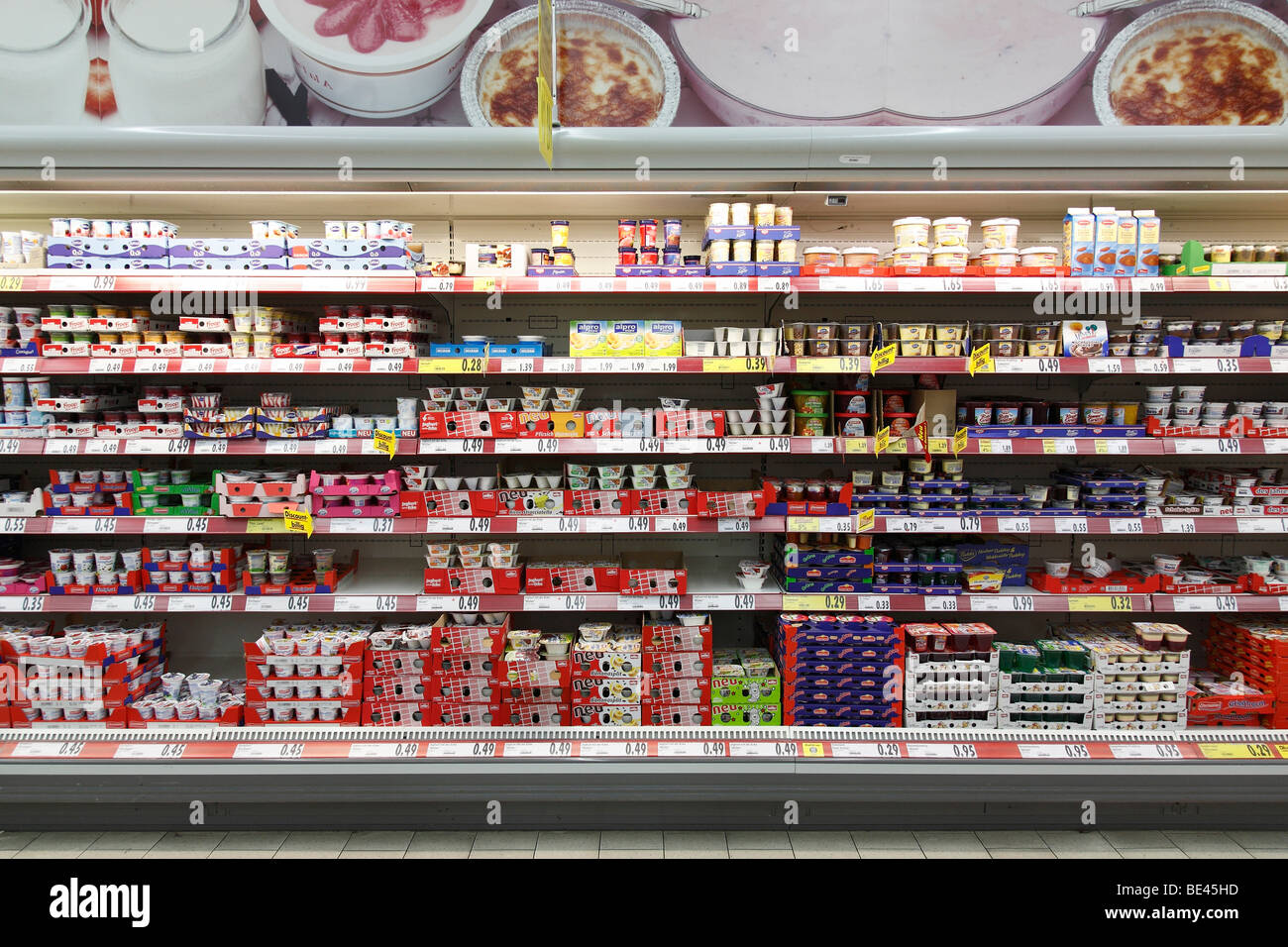shelf with yogurt cups in a supermarket - Stock Image