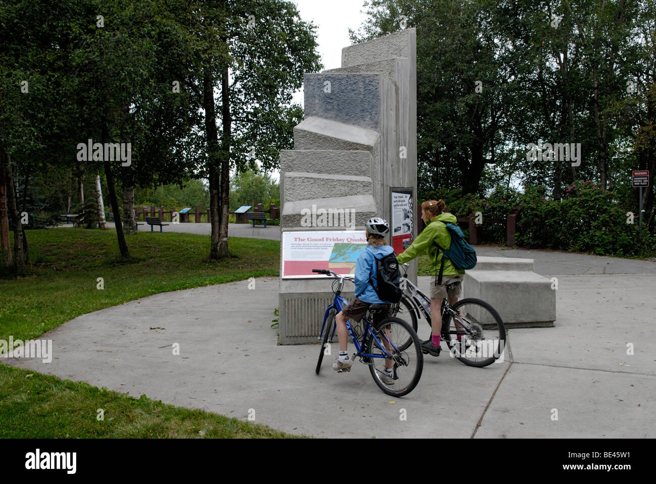 Mother and daughter reading memorial at Earthquake Park, along the Coastal Trail Anchorage, Alaska. - Stock Image