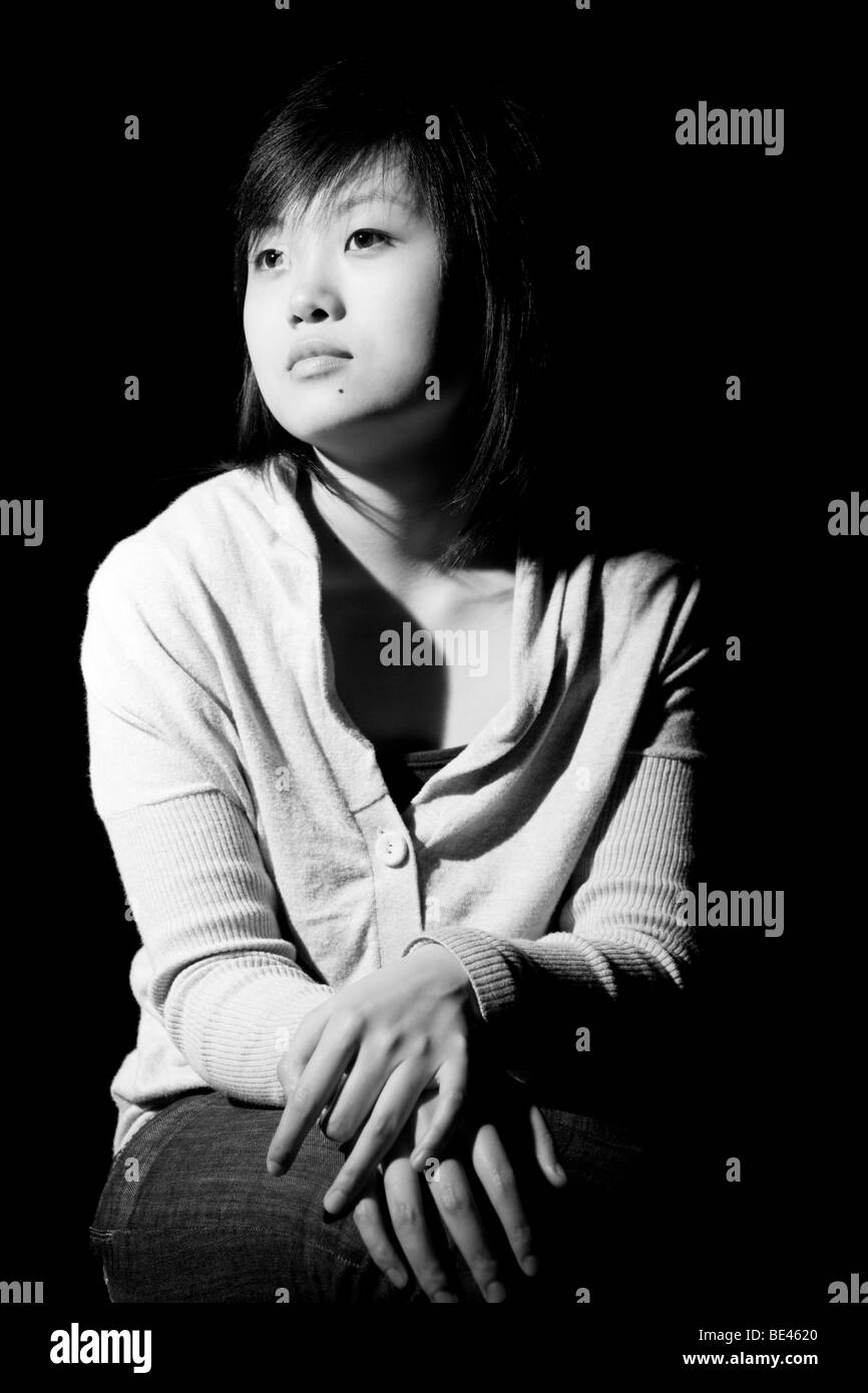 Young Chinese woman sitting with hands crossed on her lap in a thoughtful way. - Stock Image