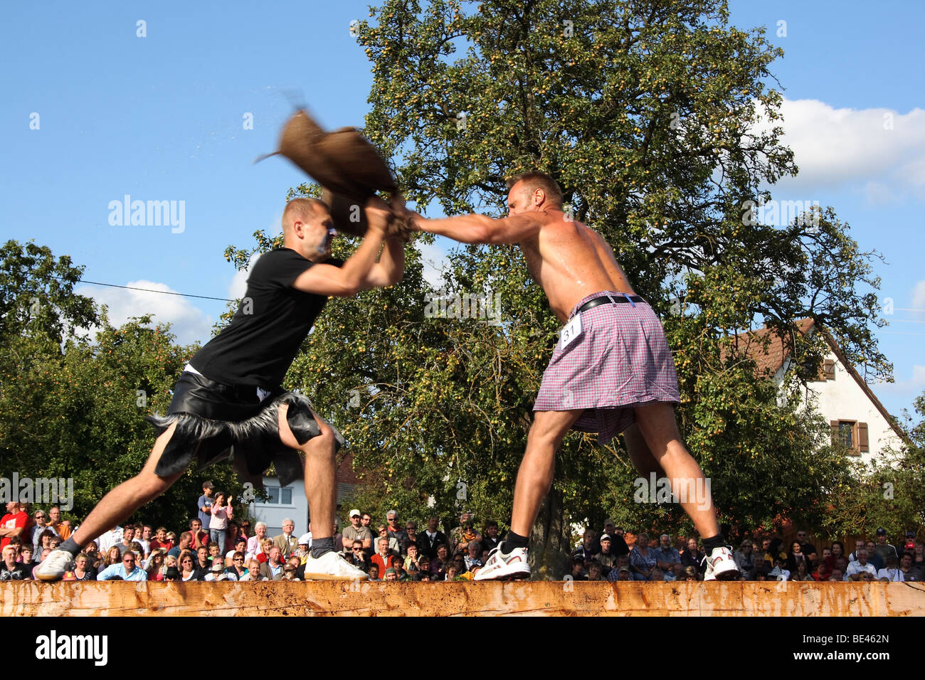 Discipline straw sack competition, straw sacks are used to push the the opponent off balance, so that he falls into - Stock Image