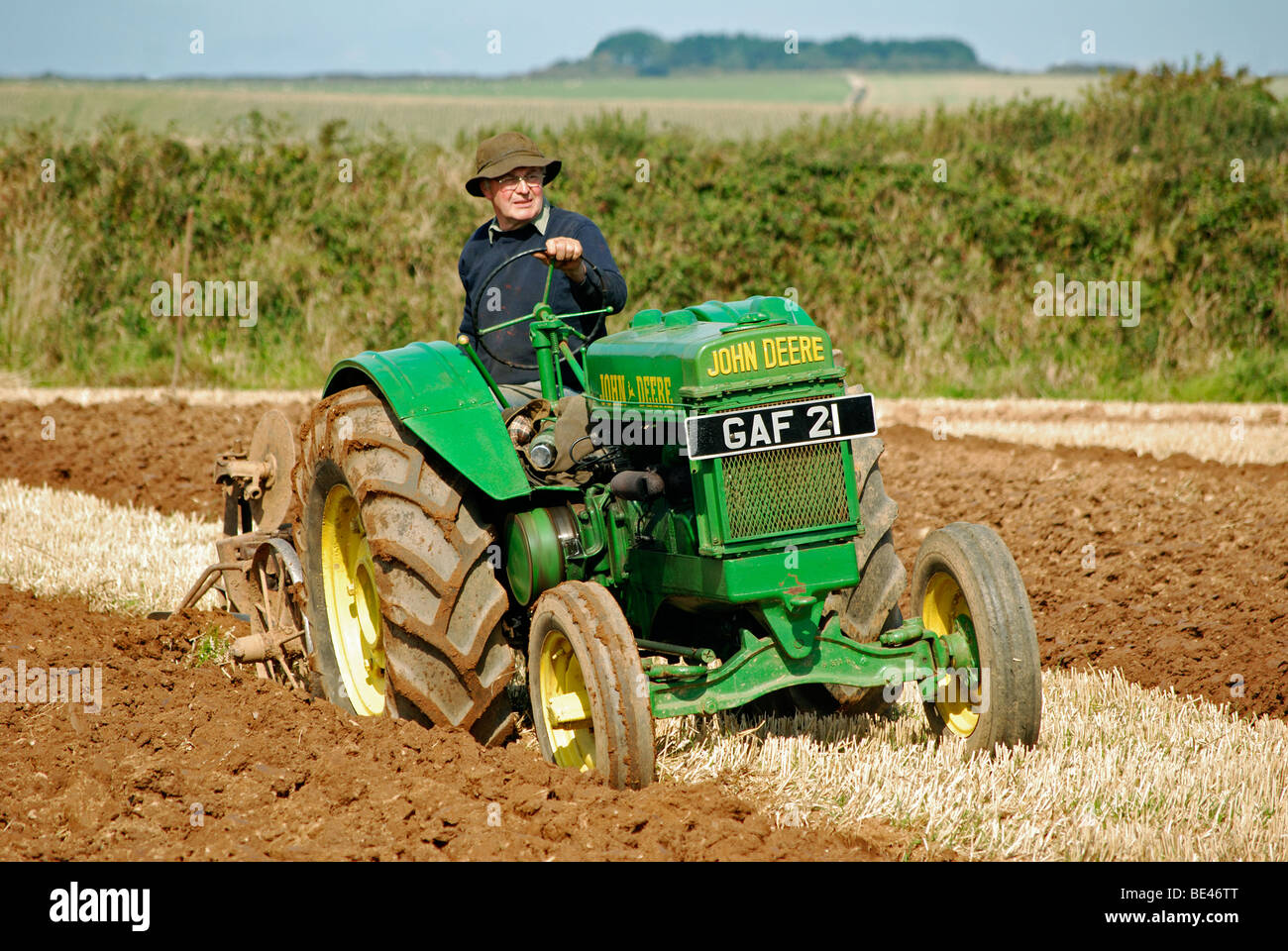 a farmer ploughing a field using an old tractor,cornwall,uk - Stock Image