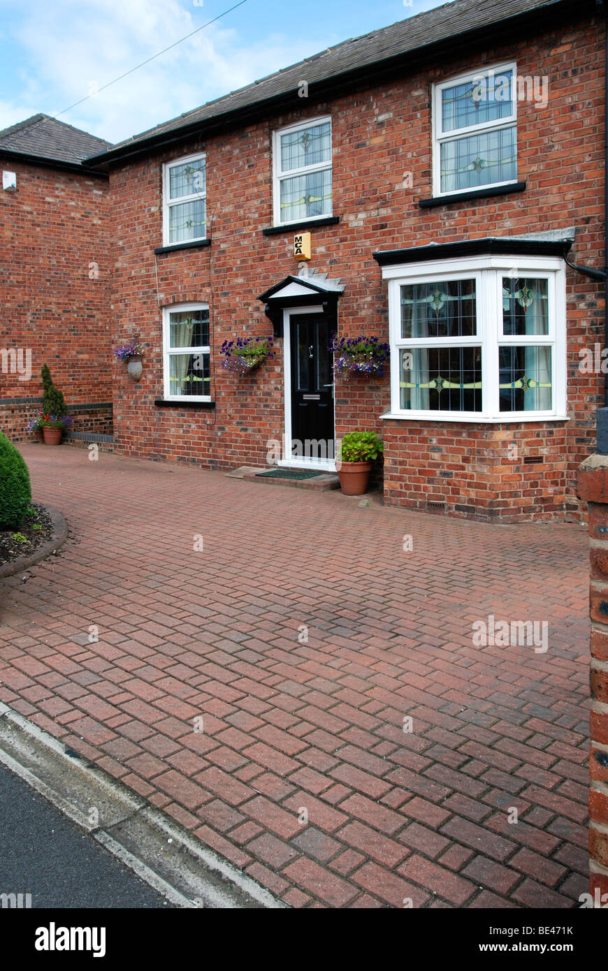 a front garden paved over with block paving stones, uk - Stock Image