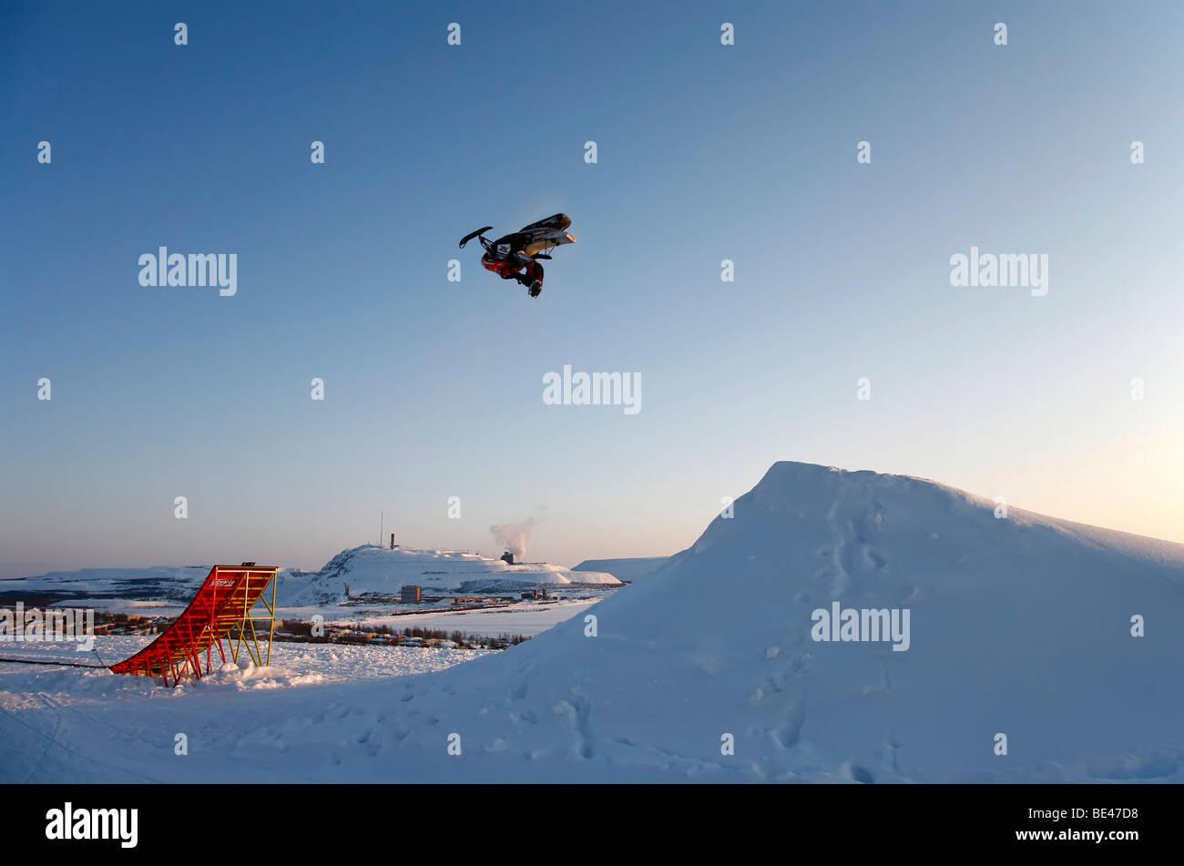 Somersaulting snowmobile in front of an ore mine in Kiruna, Sweden, Scandinavia, Europe Stock Photo