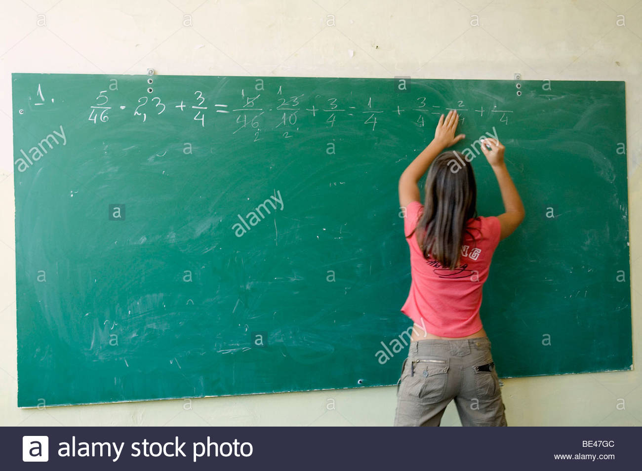 Serbia, Kosovo - Rear view of a girl writing on a blackboard Stock Photo