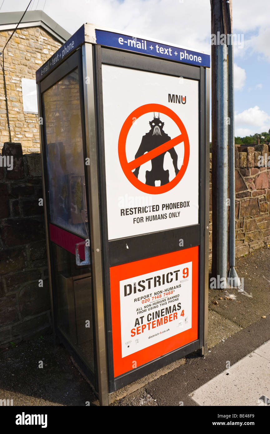 Billboard for District 9 cinema film on BT telephone box in UK RESTRICTED PHONEBOX FOR HUMANS ONLY - Stock Image