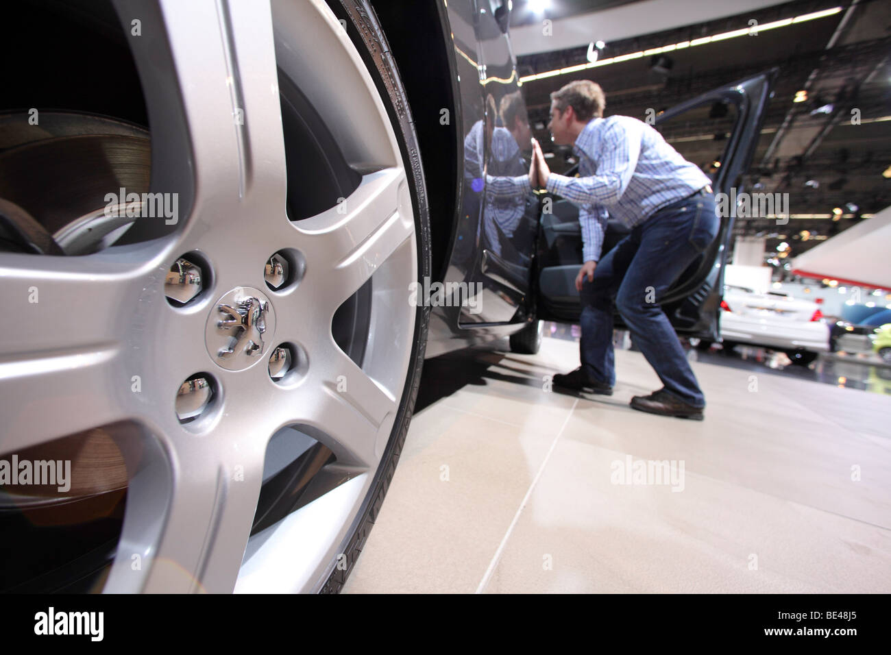 63th International Motor Show ( IAA ): A visitor is interested in a car of the manufacturer Peugeot - Stock Image