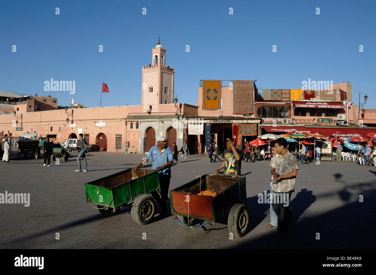 Daily Wage Labourers Pushing Hand Carts on Djemaa El-Fna Square Marrakesh Morocco - Stock Image