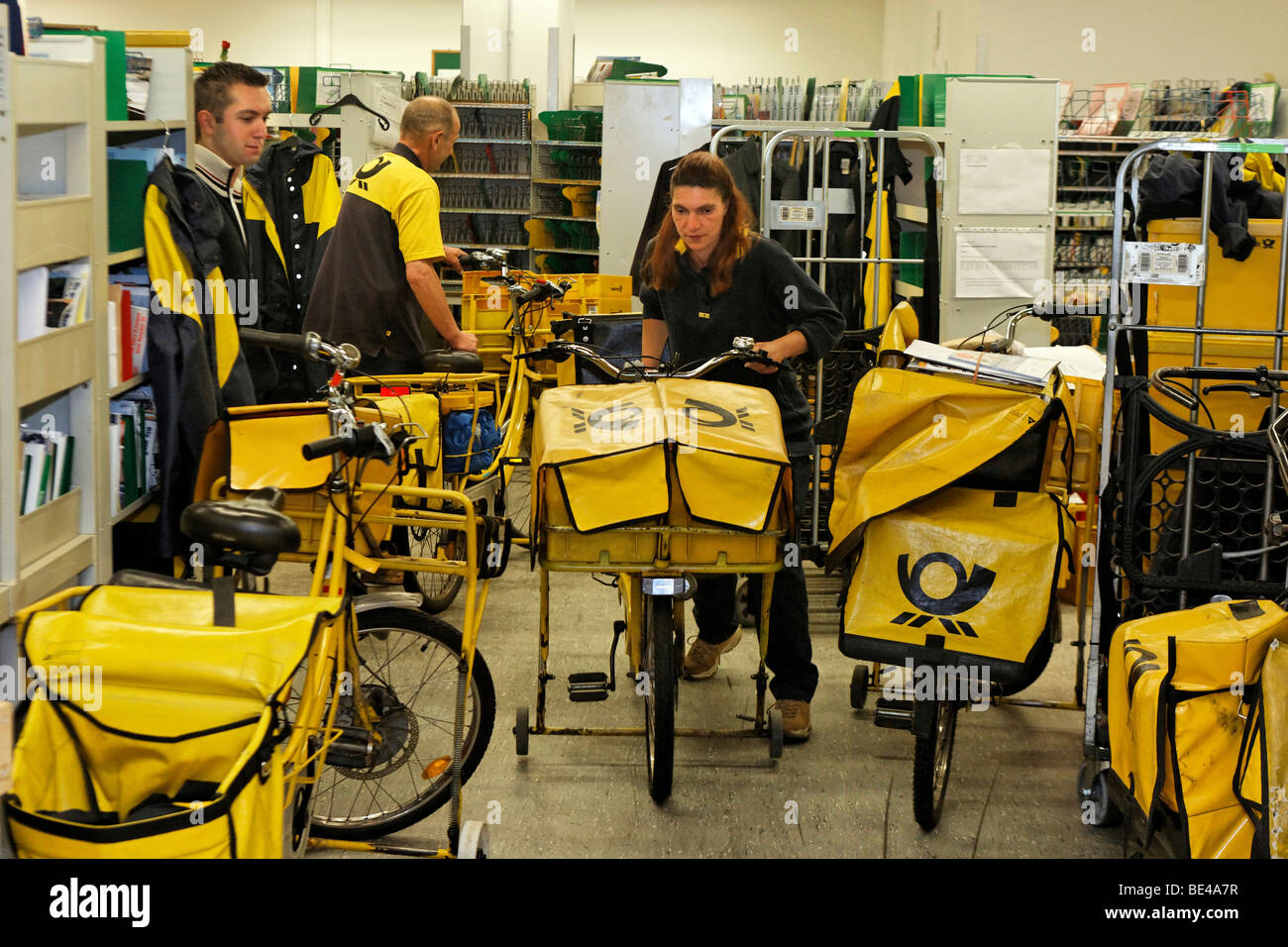 Mail carrier Annerose Schulze pushes her bicycle in the postal service distribution center of the Deutsche Post Stock Photo
